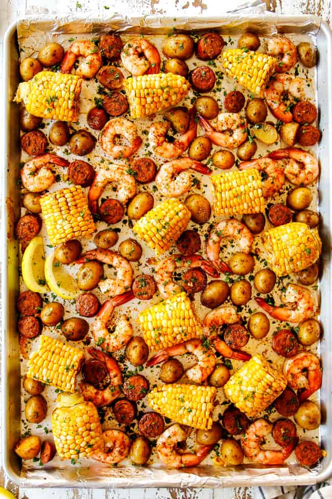 showing how to make shrimp boil recipe by baking shrimp, corn, sausage and potatoes on a sheet pan until cooked through