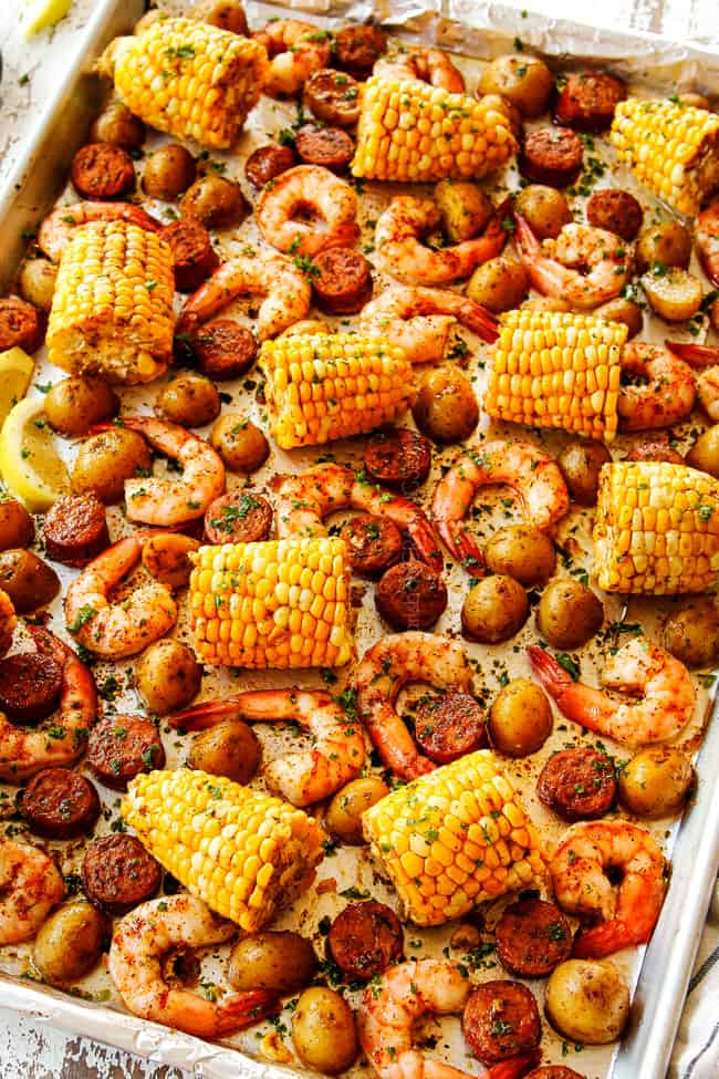 showing how to make sheet pan shrimp boil recipe by drizzling corn, potatoes, sausage and shrimp with lemon juice