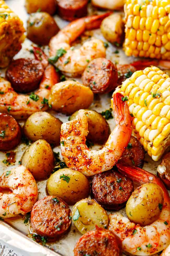 showing how to season shrimp boil recipe by adding sprinkling Old Bay seasoning over the sheet pan