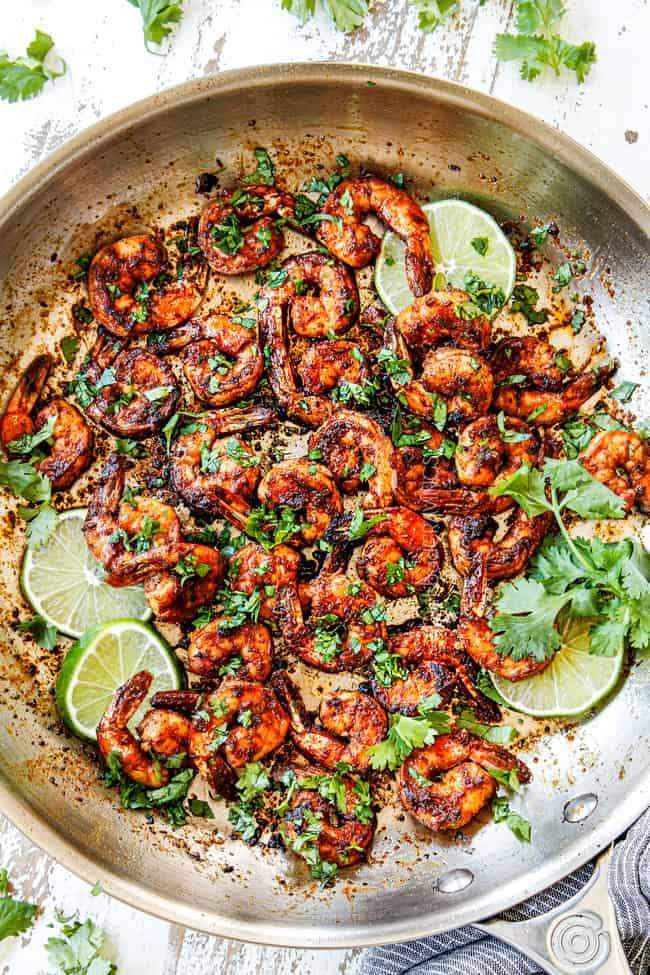showing how to make jerk shrimp by cooking shrimp in a skillet and garnishing with parsley