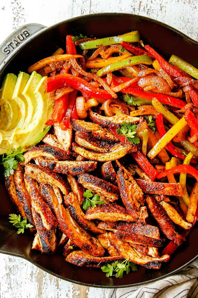 showing how to make chicken fajitas by combining sliced chicken, sliced bell peppers and sliced onions in cast iron skillet