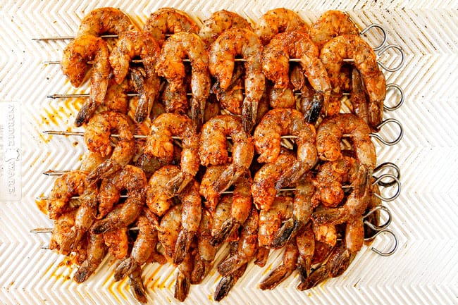 showing how to make grilled shrimp recipe by skewering marinated shrimp on metal skewers then lining on a baking sheet
