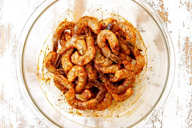 showing how to make grilled shrimp recipe by adding shrimp to a glass bowl and stirring to combine with marinade