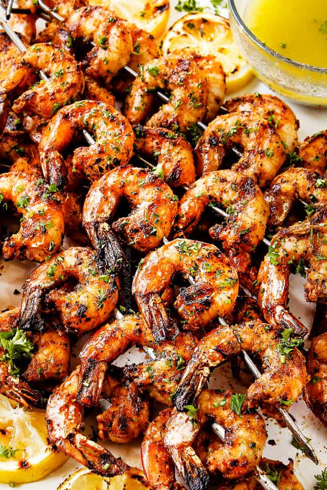 a stack of lightly charred grilled shrimp skewers on a white plate garnished by parsley
