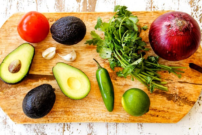 showing how to make best guacamole recipe by laying out ingredients on a wood cutting board: avocados, tomatoes, garlic, jalapenos, cilantro, lime and red onion