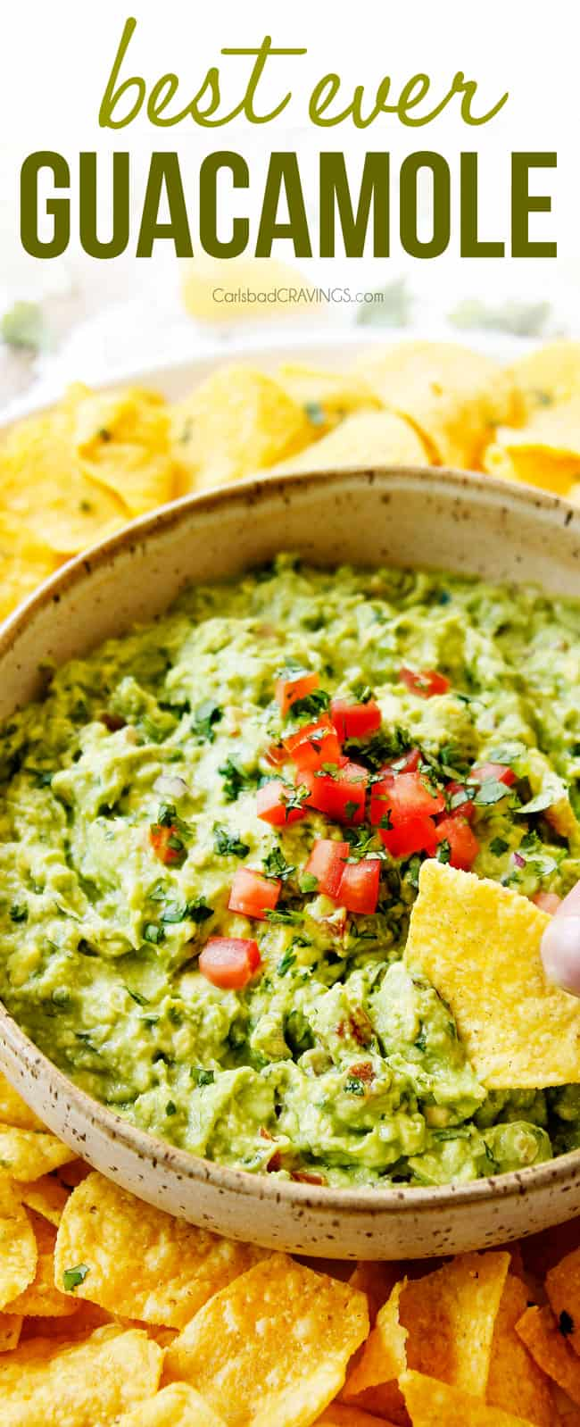 showing how to eat homemade guacamole by dipping a chip into the guacamole in a tan bowl surrounded by tortilla chips