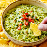 showing how tot make guacamole by tasting guacamole with a tortilla chip