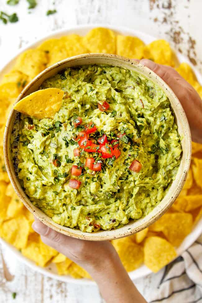 showing the texture of chunky guacamole by holding a bowl up with two hands