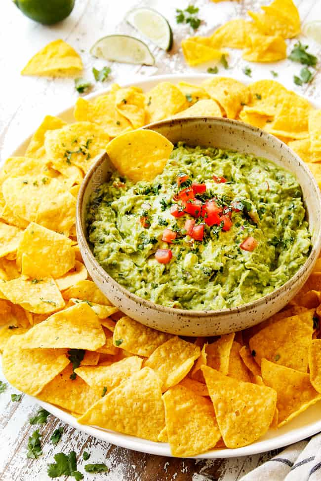 showing how to serve homemade guacamole by adding to a tan bowl and serving with tortilla chips