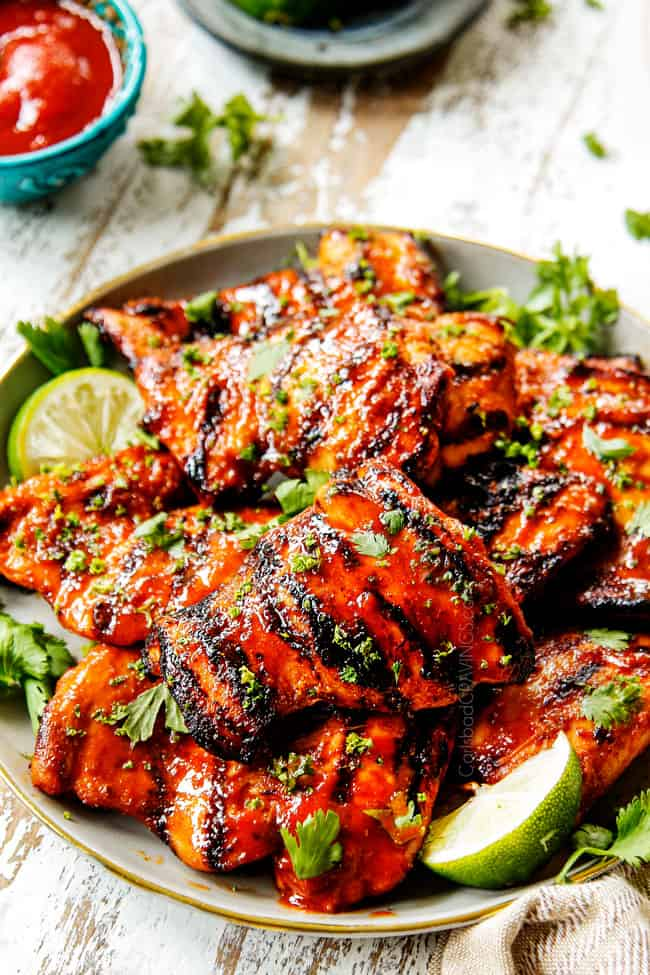 Honey Sriracha Chicken recipe with grill marks on a grey plate with limes