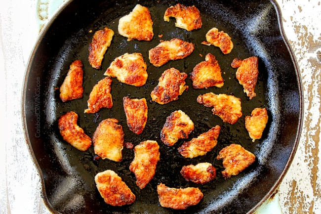 showing how to make Hunan chicken by adding lightly breaded chicken to a cast iron skillet