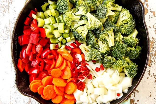 showing which vegetables you add to Hunan style chicken  by adding broccoli, carrots, celery, carrots, bell peppers and chili peppers to a cast iron  skillet in separate groups