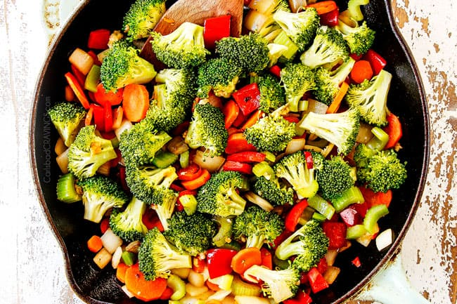 showing how to make Hunan chicken by adding broccoli, carrots, celery, carrots, bell peppers and chili peppers to skillet