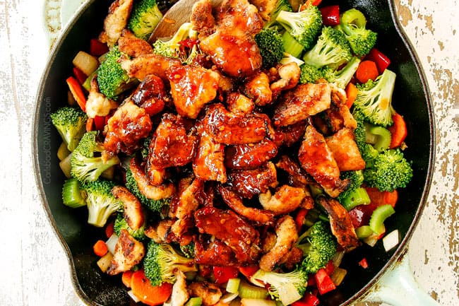 showing how to make Hunan chicken by adding Hunan sauce to skillet with stir fried veggies
