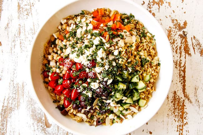 showing how to make orzo pasta salad recipe by adding orzo, cucumbers, bell peppers, tomatoes, olives, chickpeas, basil and feta to a large glass bowl