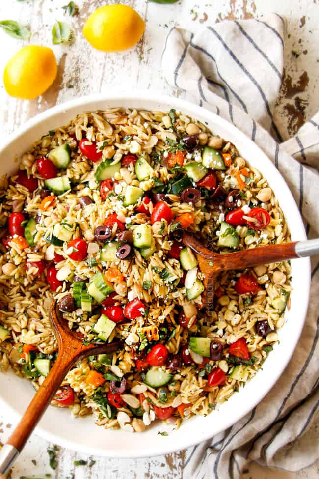 showing how to make Greek orzo pasta salad by adding tossing orzo, cucumbers, bell peppers, tomatoes, olives, chickpeas, basil and feta together with dressing in a white bowl
