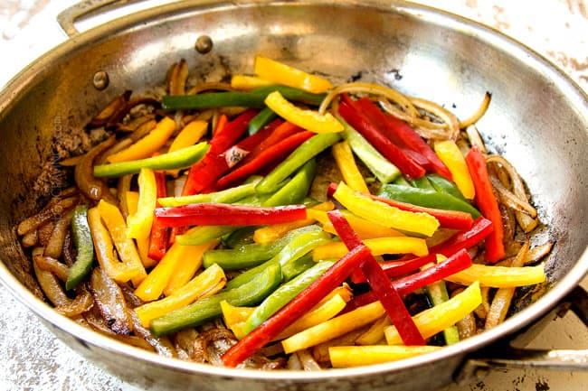 showing how to make Pepper Steak recipe by stir frying red, yellow and green bell peppers in a stainless steel pan