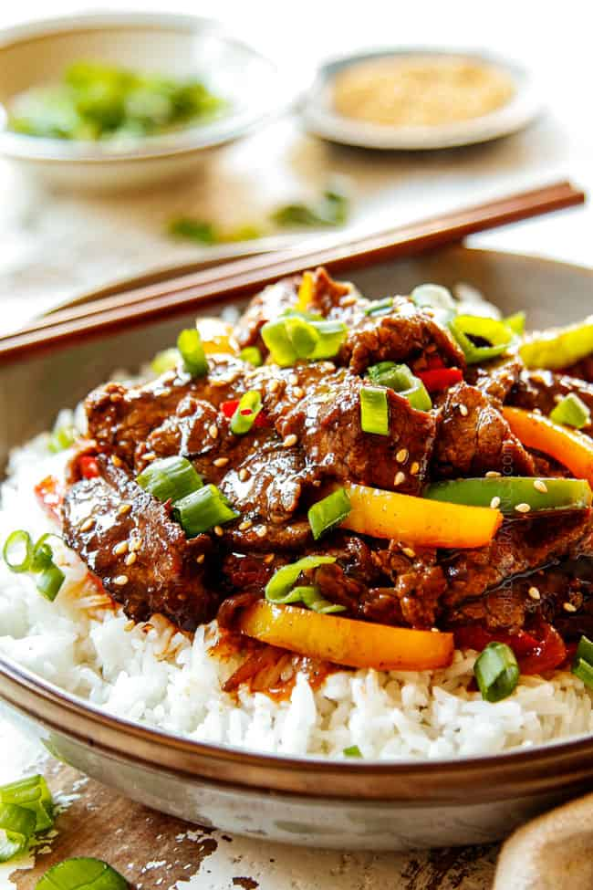 showing how to serve Pepper Steak recipe by adding to a bowl of white rice