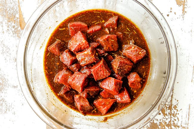 showing how to make steak kabobs by adding cubed top sirloin to a glass bowl in the steak marinade