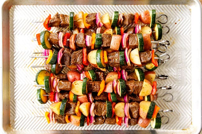showing how to make steak kabobs by assembling steak and vegetables onto skewers and stacking on a baking sheet