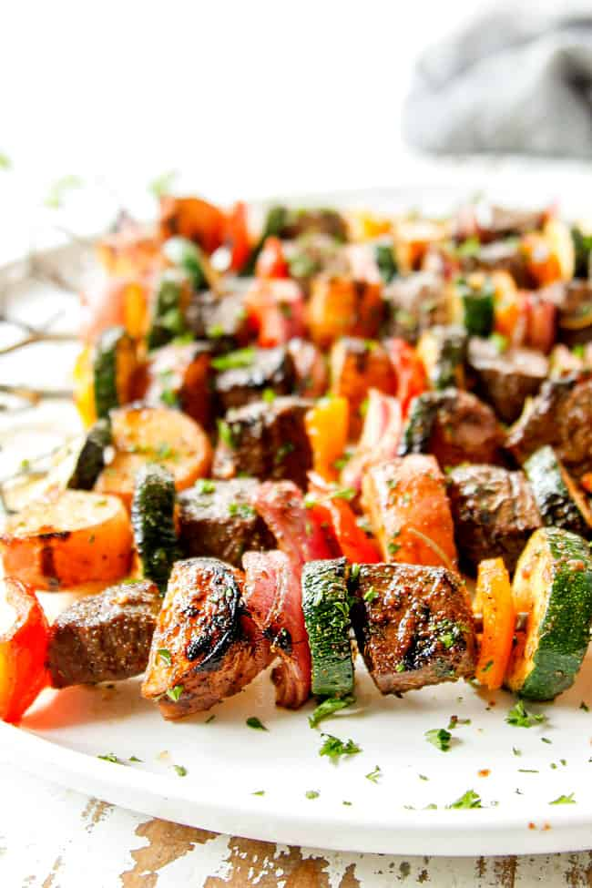 up close of steak kabobs on a white platter showing how juicy they are