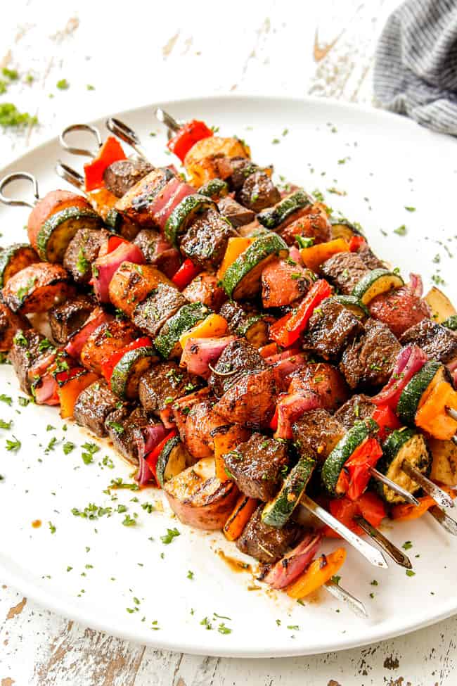 showing how to garnish steak kabobs with bell peppers, onions and zucchini by sprinkling skewers with  parsley