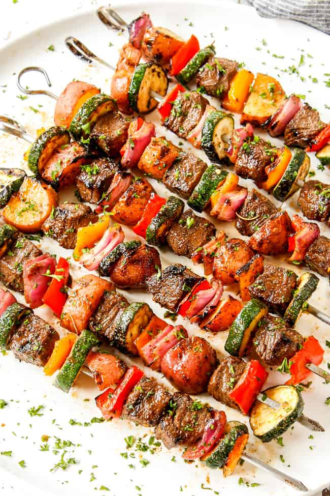 beef kabobs that have been marinated lined in a row on a white platter