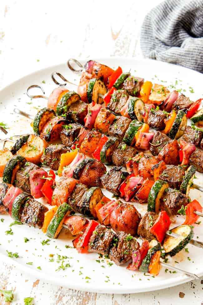 showing how to serve beef kabobs by lining on  a plate and garnishing with parsley