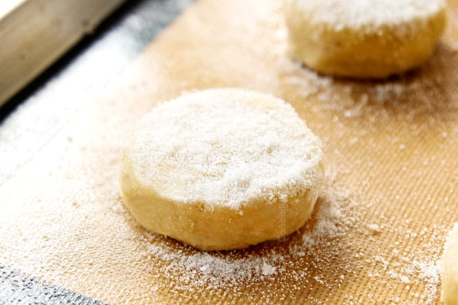 showing how to make Strawberry Shortcake by adding sugar to biscuit rounds on a nonstick mat