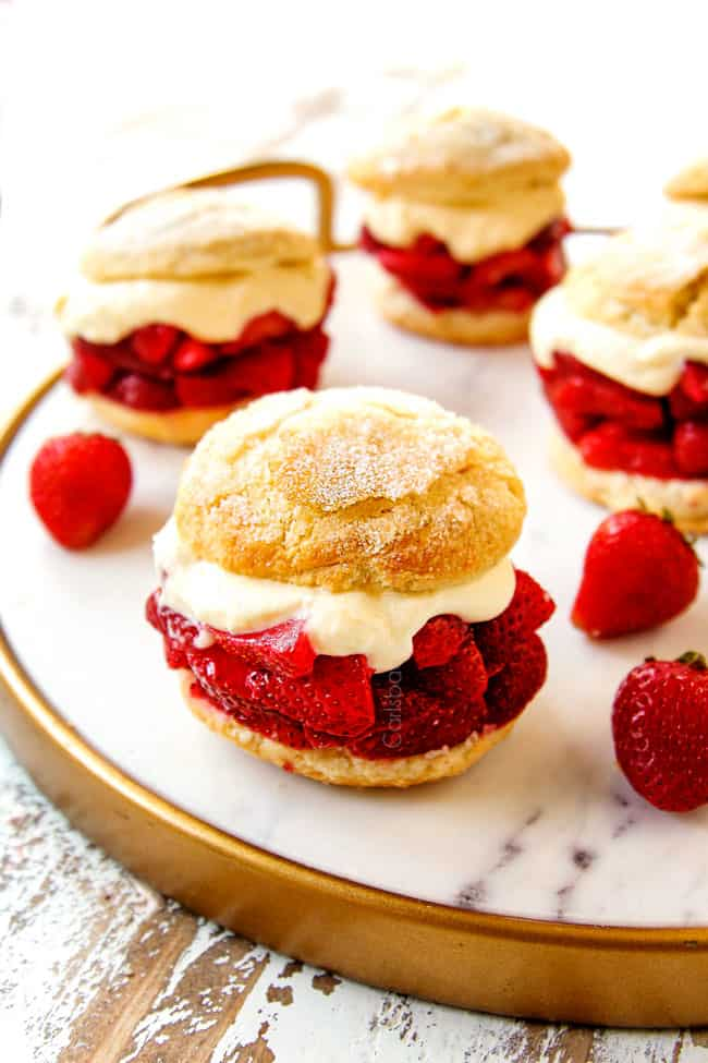 showing how to serve strawberry shortcake by layering biscuits with strawberries, whipped cream and topping with half a biscuit and placing on a white marble platter