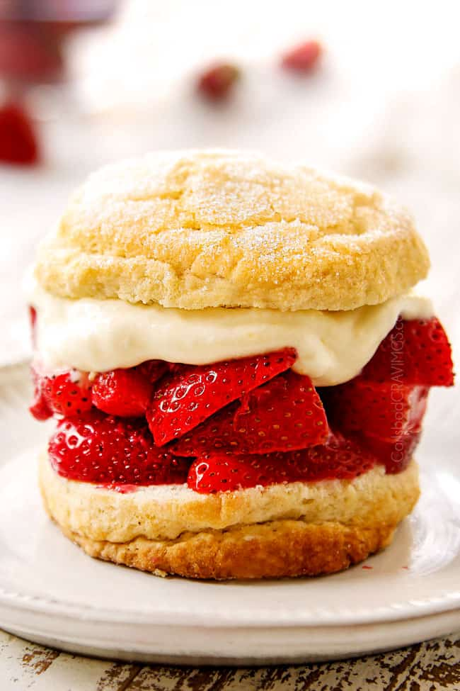 showing how to make strawberry shortcake by adding whipped cream on top of strawberries and topping with a biscuit