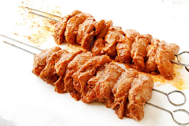 showing how to make doner kebab by threading chicken onto skewers