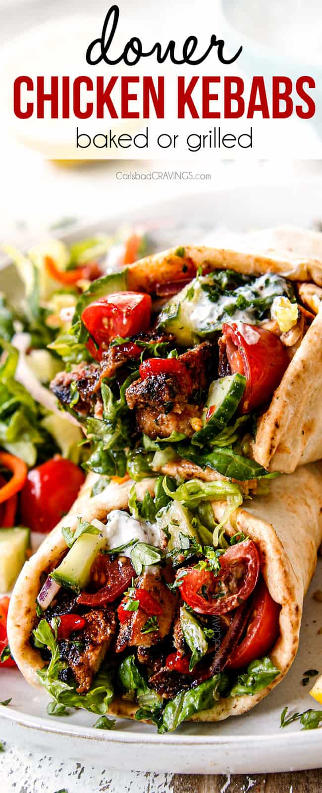 up close of doner kebab with chicken, hummus, tomatoes, red onions, cucumber and yogurt sauce
