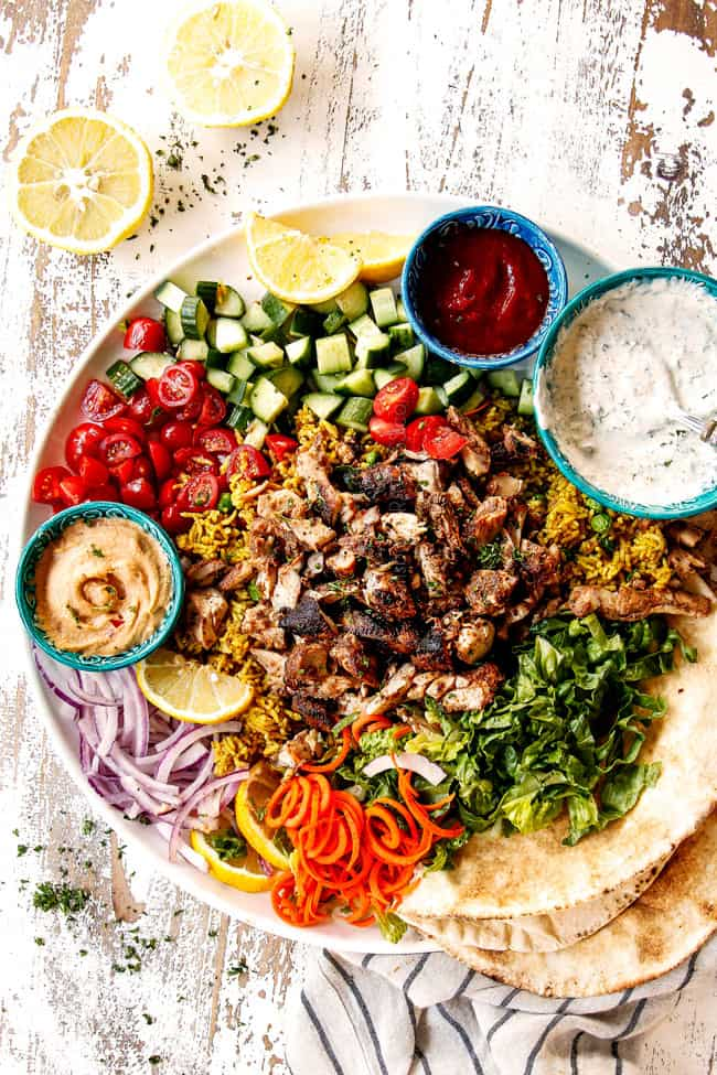 top view of doner kebab plate with thinly sliced meat, thinly sliced lettuce, thinly sliced red onions, chopped tomatoes, chopped cucumber, Lebanese flatbread and garlic yogurt sauce