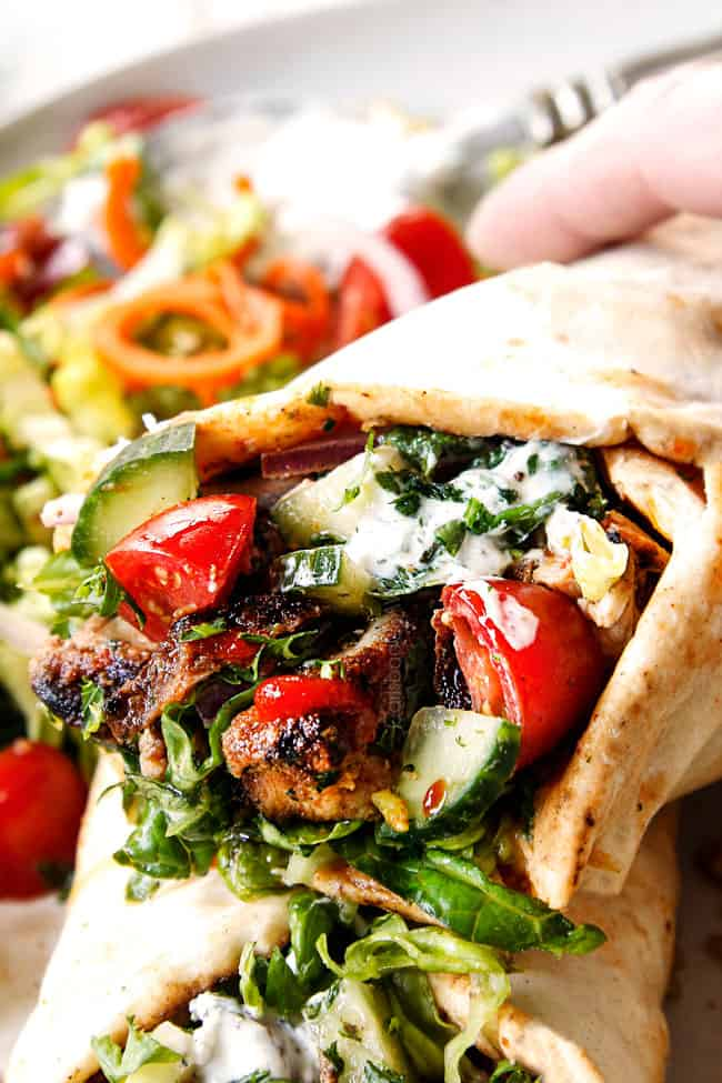 up close of doner kebab wraps with thinly sliced meat to Lebanese flatbread  with hummus, thinly sliced lettuce, thinly sliced red onions, chopped tomatoes, chopped cucumber, chili sauce and garlic yogurt sauce