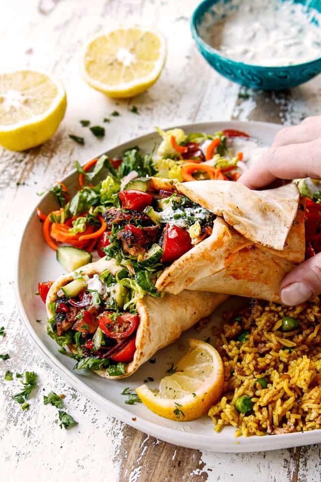 showing how to serve doner kebab meat by adding to flatbread with hummus, thinly sliced lettuce, thinly sliced red onions, chopped tomatoes, chopped cucumber, Lebanese flatbread, chili sauce and garlic yogurt sauce