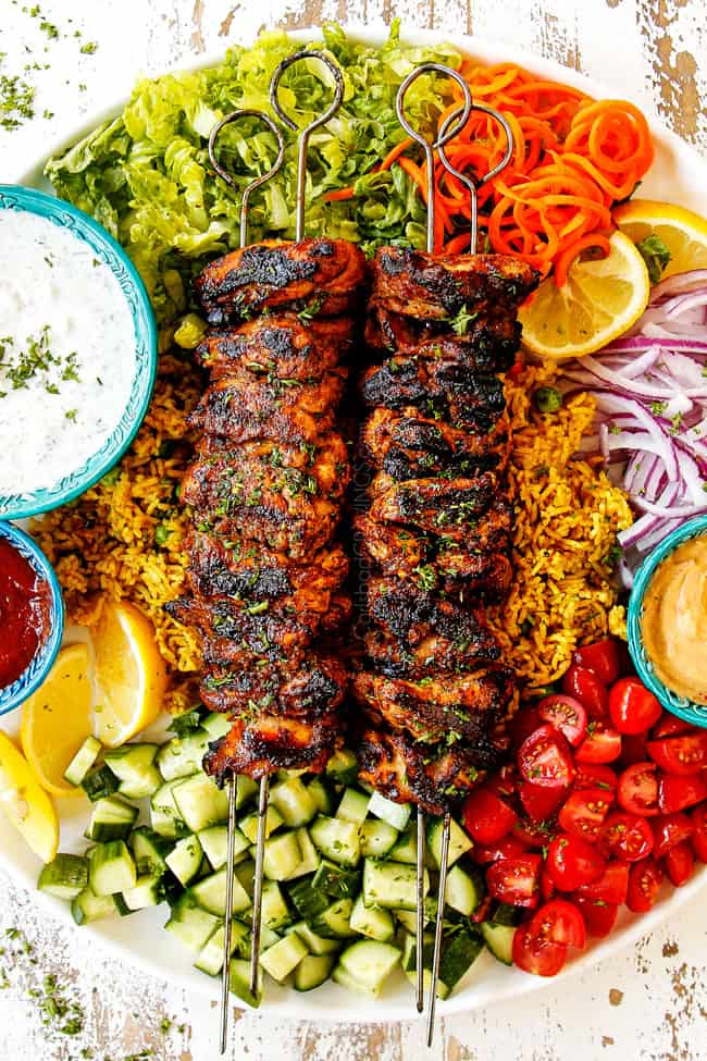 top view showing how to serve doner kebab meat by adding kebabs to a plate with hummus, thinly sliced lettuce, thinly sliced red onions, chopped tomatoes, chopped cucumber, curried rice, Lebanese flatbread, chili sauce and garlic yogurt sauce