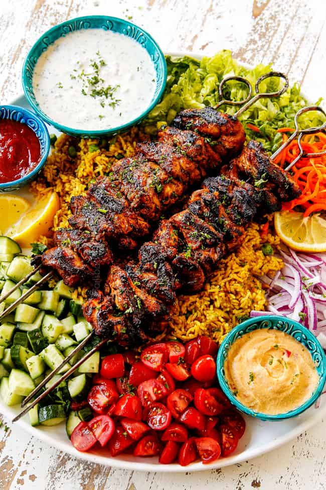 showing how to make doner kebab plates by adding kebabs to a platter with rice, lettuce, red onions, tomatoes and cucumbers