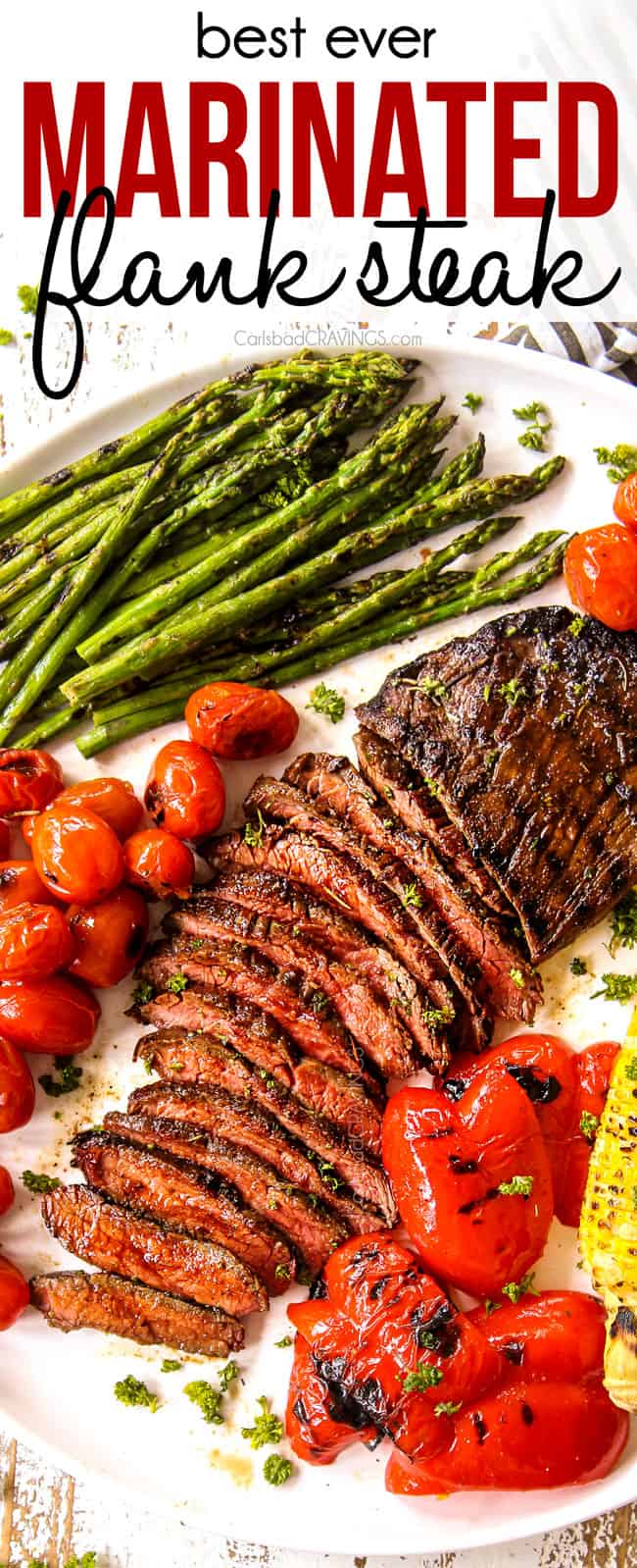 top view of flank steak recipe cut in thin slices on a white platter with grilled corn and asparagus