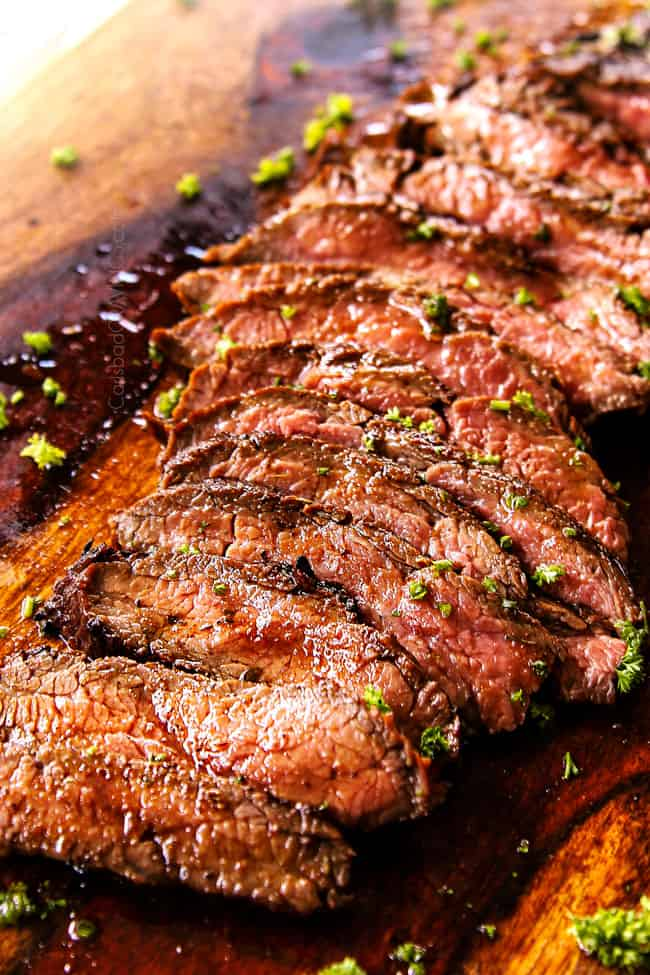 up close of grilled marinated flank steak recipe on a cutting board cut into thin strips showing how to cut the steak against the grain