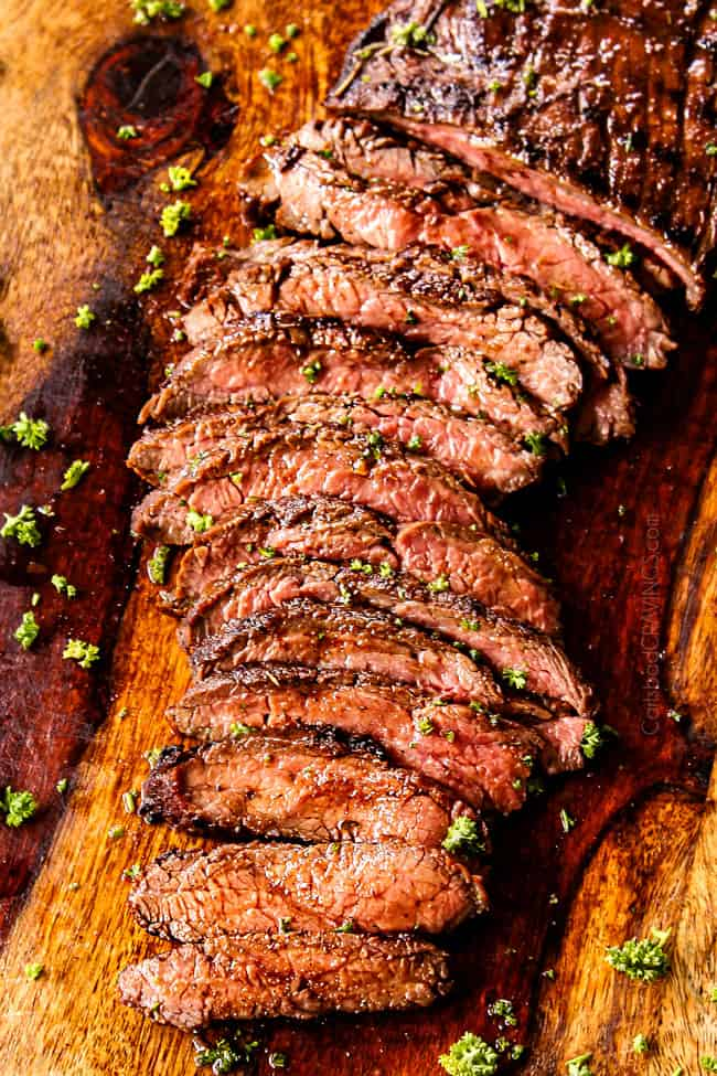 top view of grilled flank steak on a cutting board garnished with parsley