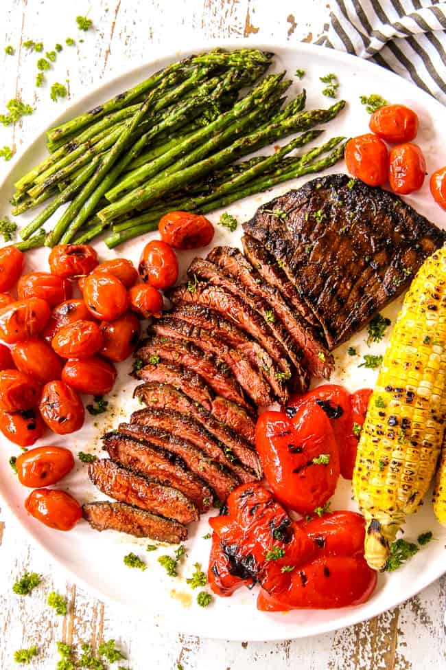 top view of flank steak cut in thin slices on a white platter with grilled corn and asparagus and bell peppers showing how to serve