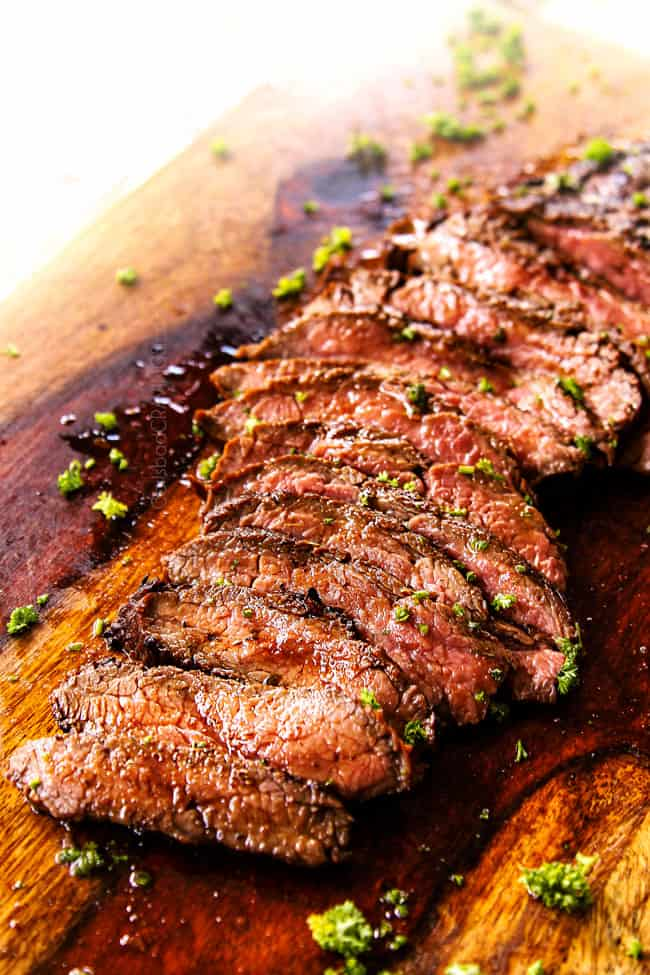 marinated flank steak on a cutting board cut into thin strips showing how juicy it is