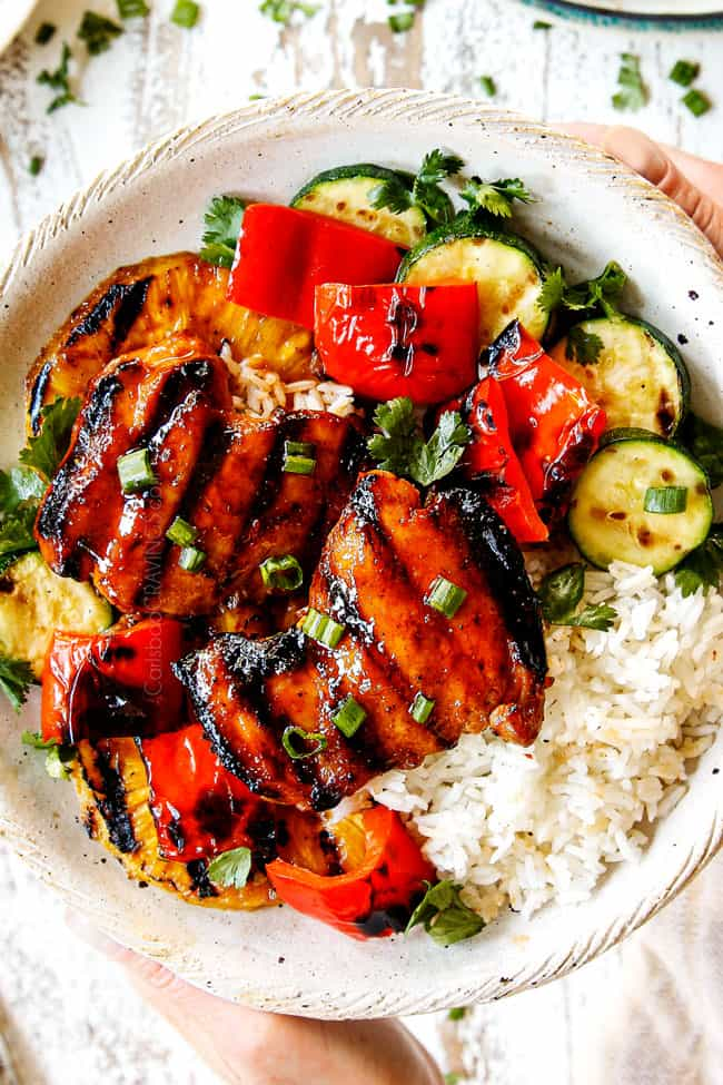 top view of two hands holding a cream plate of Hawaiian chicken with white rice, grilled bell peppers and zucchini