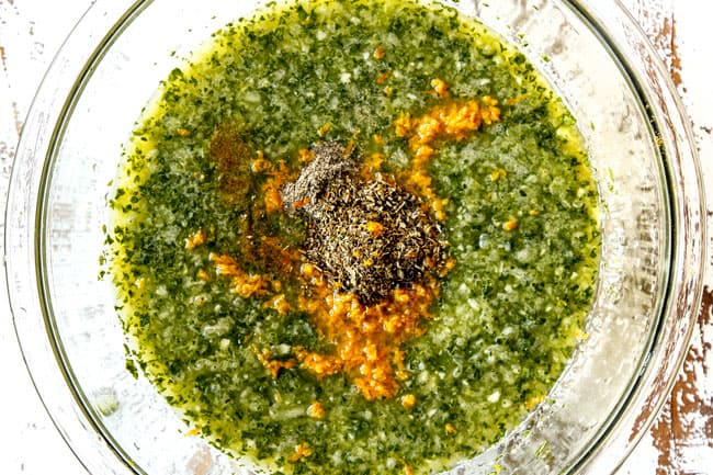 showing how to make mojo marinade by adding orange juice, oregano, ground cumin, orange zest, finely chopping onion, garlic, cilantro and jalapeno to a large glass bowl