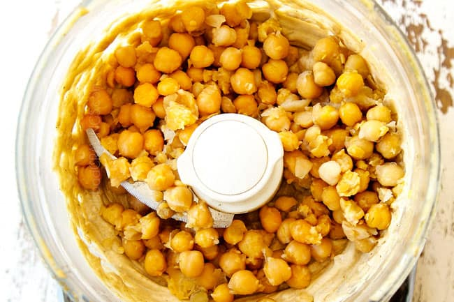 showing how to make hummus by adding chickpeas to food processor