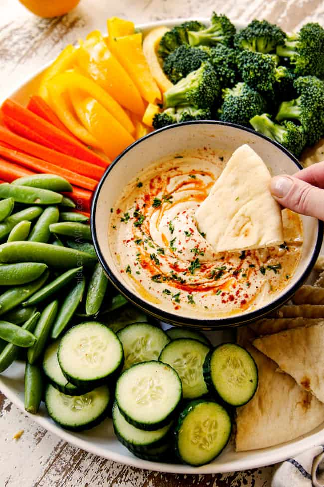 showing how to serve hummus recipe by adding hummus recipe to a black bowl with a platter of broccoli, cucumbers, snap peas, carrots, pita bread and bell peppers