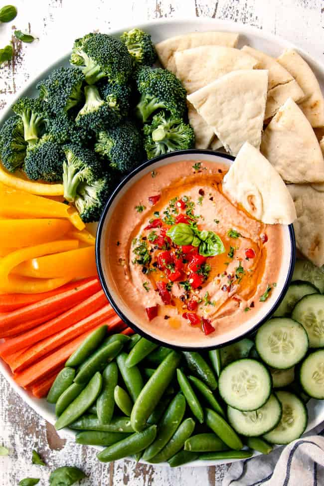 top view of hummus in a black bowl on a platter with carrots, broccoli, cucumbers, snap peas, bell peppers and pita bread