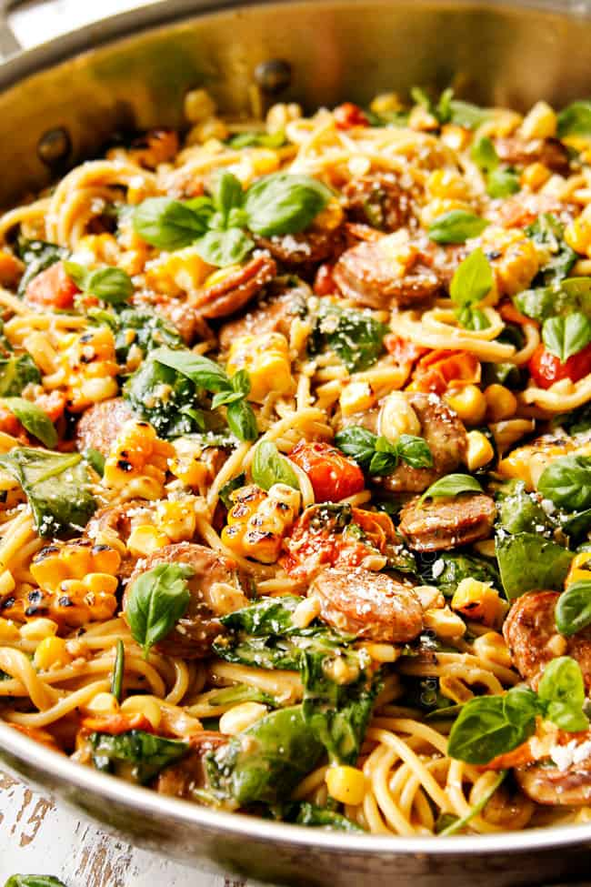 up close of creamy spinach pasta recipe with tomatoes showing how creamy it is