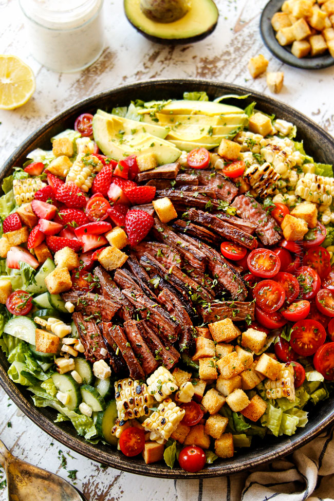 side view of steak salad recipe in a wooden bowl with sliced steak, corn, croutons, tomatoes, avocados and strawberries